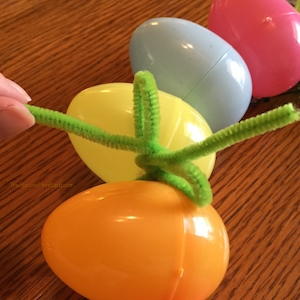 tying a pipe cleaner bow on Easter wreath