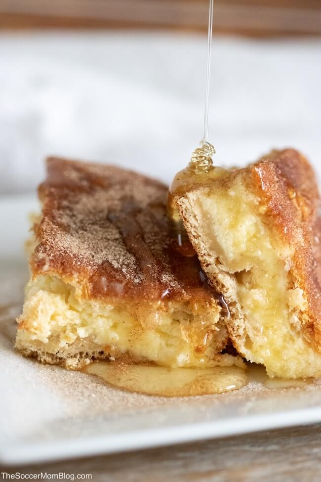Sopapilla Cheesecake Bars is one of my husband's most requested desserts of all time! Real, creamy cheesecake layered between flaky croissant dough and topped with cinnamon, sugar, and honey - it's heavenly!
