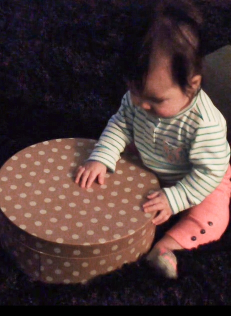 baby playing drums with a round box