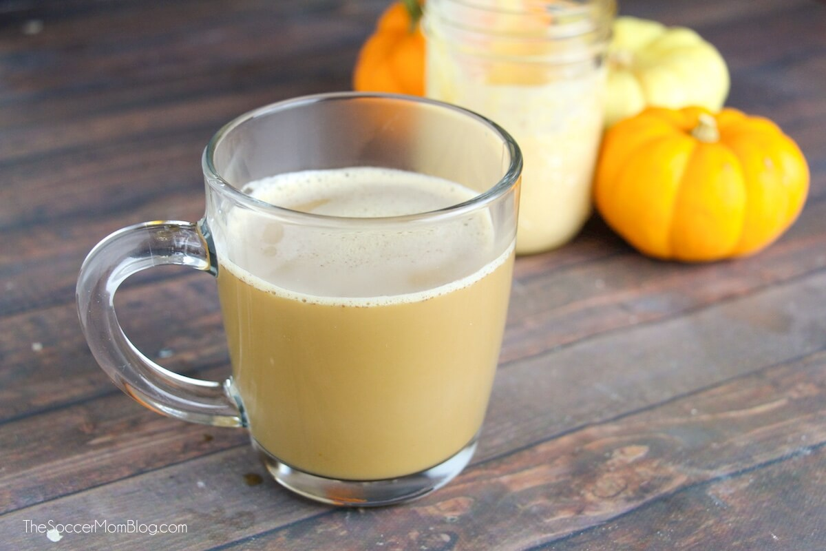 low carb pumpkin spice latte in glass mug with pumpkins in background