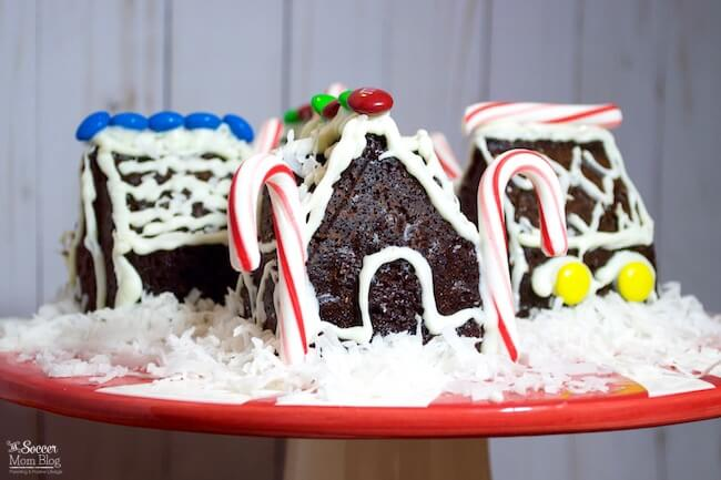These Mini Gingerbread House Cakes taste just as delicious as they look! Moist, spicy gingerbread cake (gluten free!) beautifully decorated to make a show-stopping Christmas dessert centerpiece!