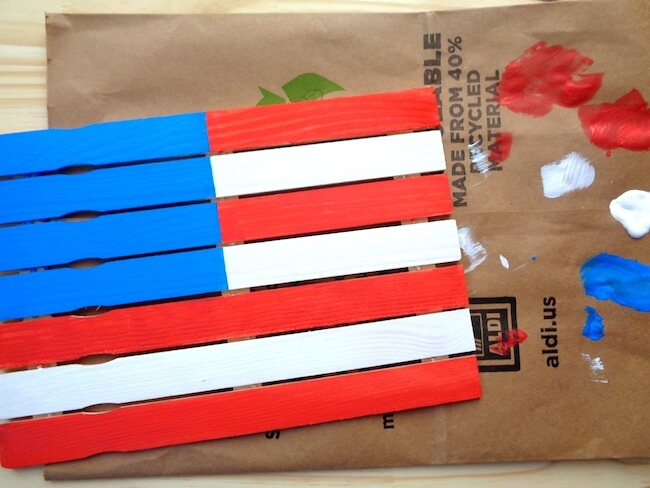 painting a wooden American flag made of paint sticks