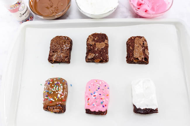 Rich, chewy brownies — dipped in chocolate and and on a stick for easy eating! These cute and clever Brownie Popsicles are the perfect party treat!