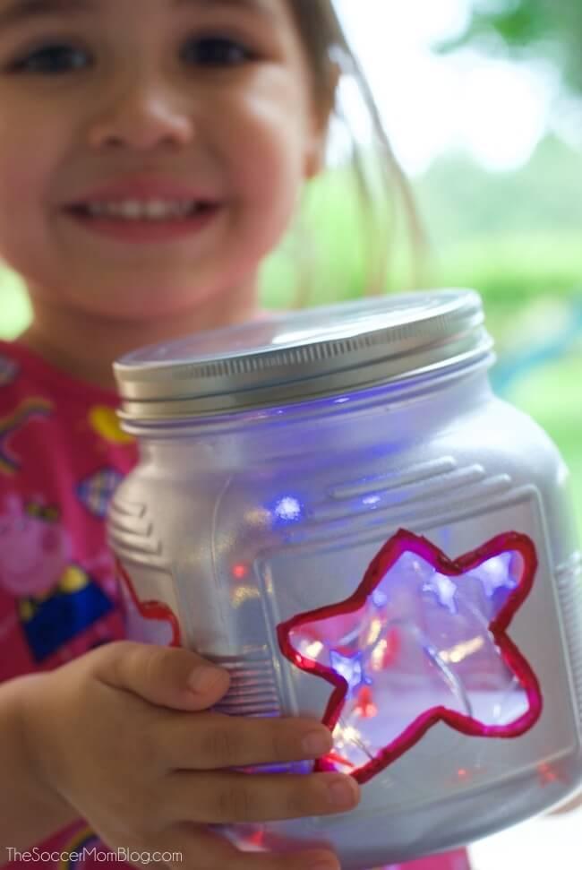 little girl holding a painted 4th of July mason jar lantern