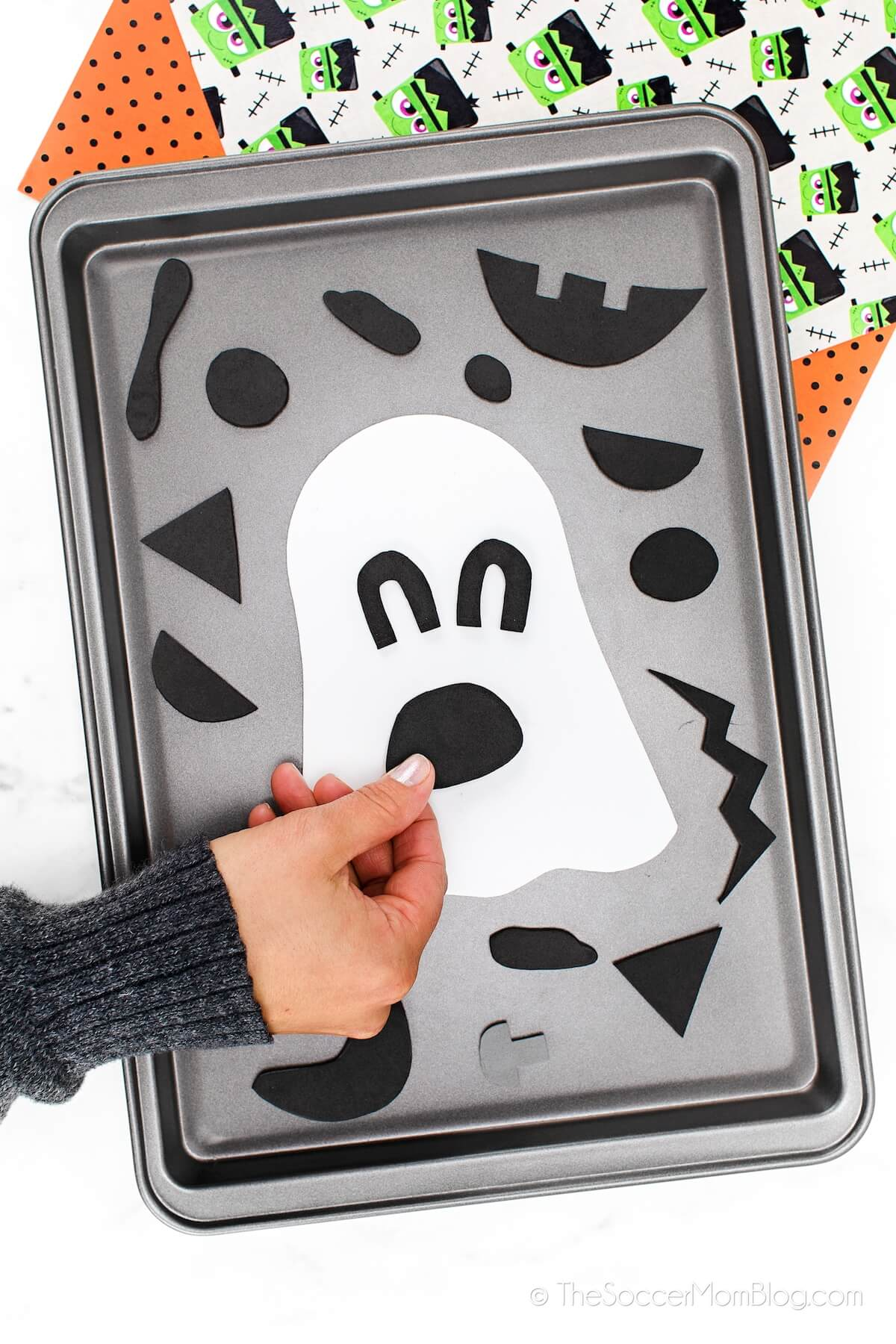 making funny faces with ghost Halloween magnet