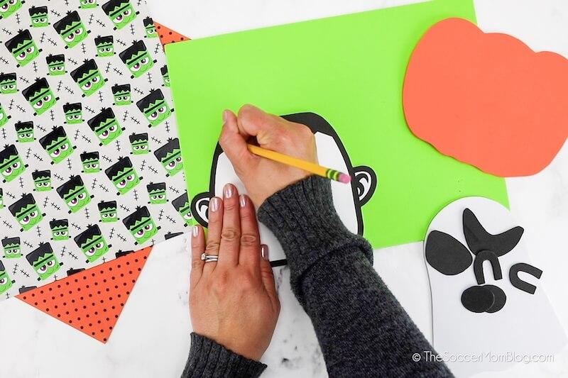 tracing a Frankenstein head onto green craft foam
