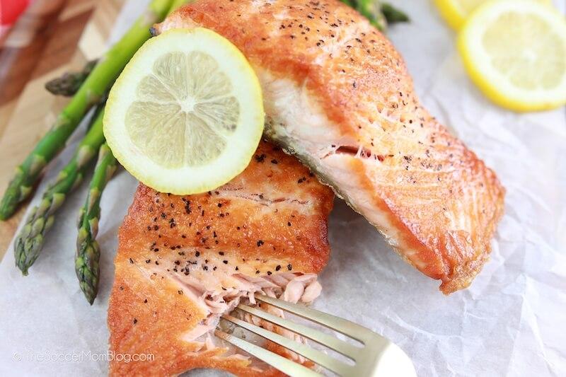 cutting into a salmon filet