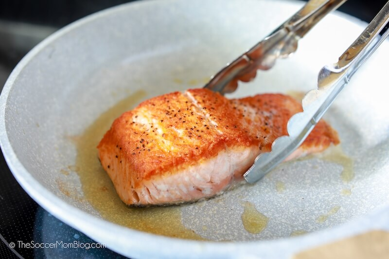 grabbing salmon with tongs to flip in pan