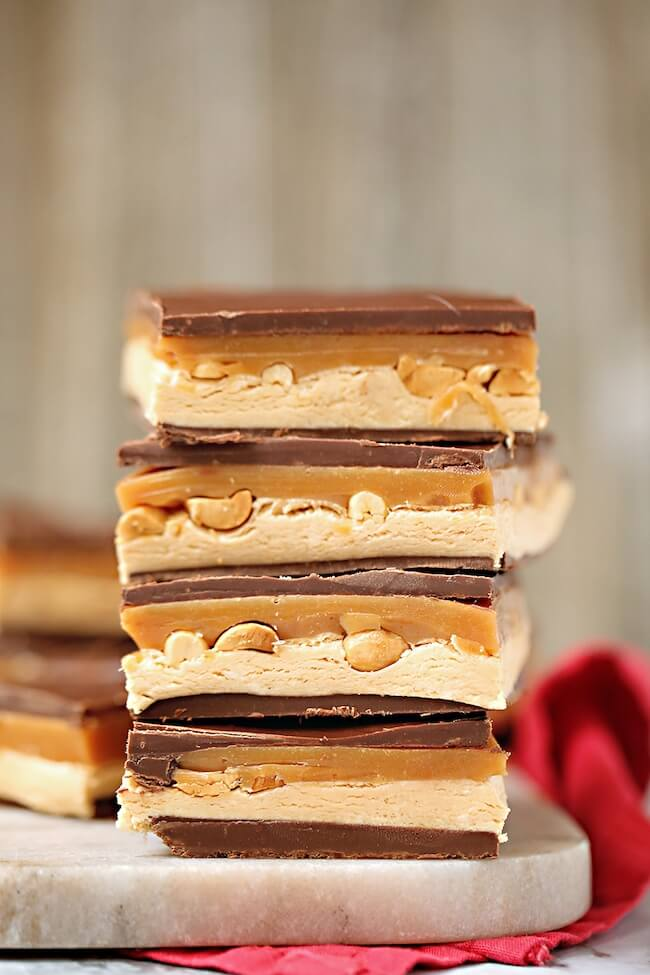 stack of homemade snickers candy bars filled with caramel and peanuts