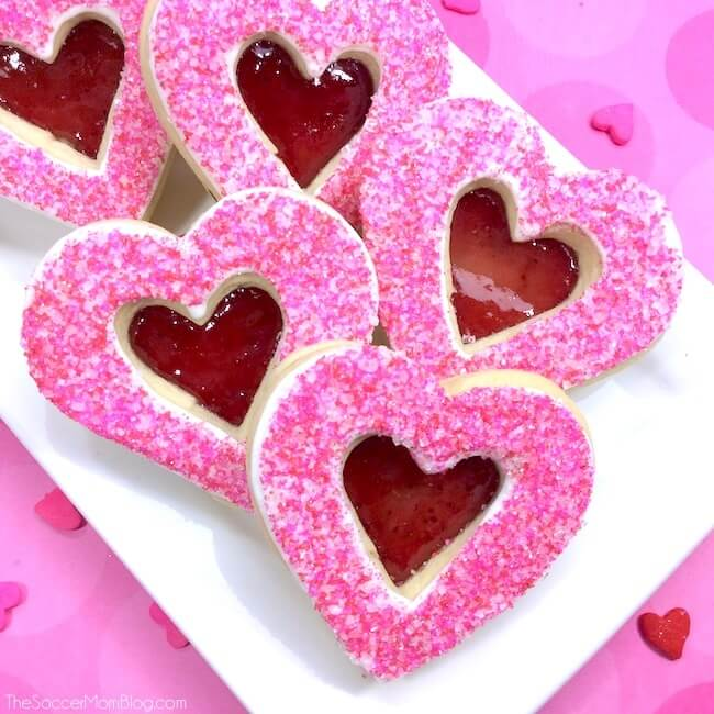 """These stained glass heart cookies make an absolutely gorgeous Valentine's Day treat! Real from-scratch sugar cookies with sparkling pink icing and a jelly """"stained glass"""" cutout center."""