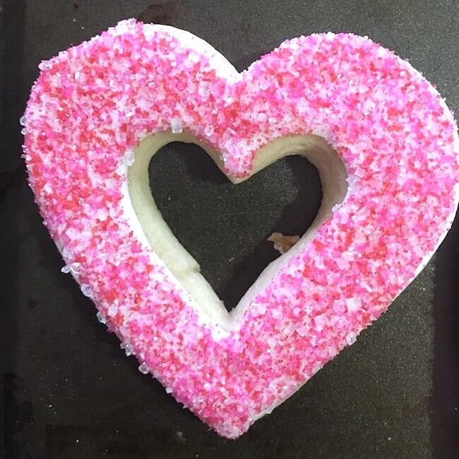 "These stained glass heart cookies make an absolutely gorgeous Valentine's Day treat! Real from-scratch sugar cookies with sparkling pink icing and a jelly ""stained glass"" cutout center."