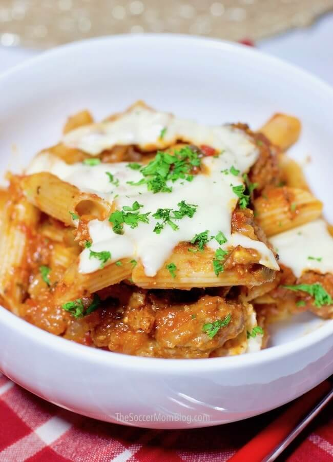 Baked penne pasta in bowl topped with cheese