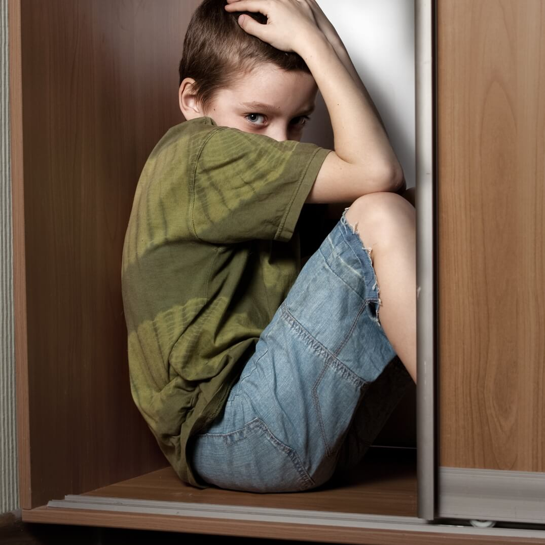 Child hiding in cabinet