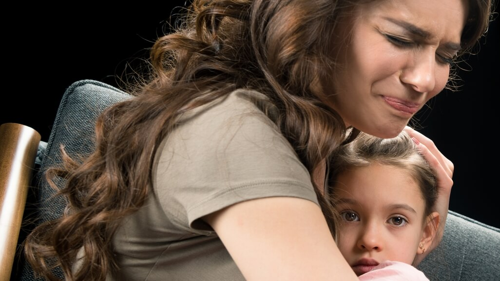 woman crying holding child