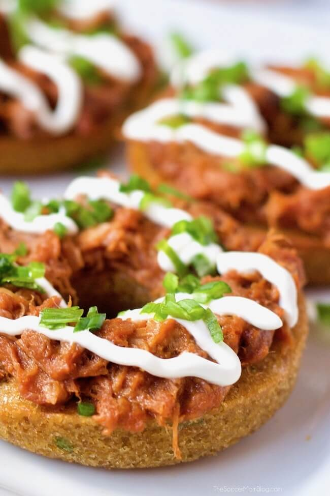 Savory barbecue sweet potato donuts topped with sour cream and green onions
