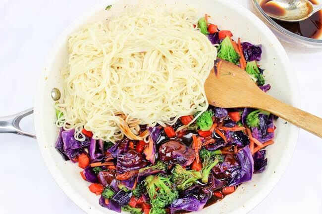 Chinese noodles added to vegetables in skillet