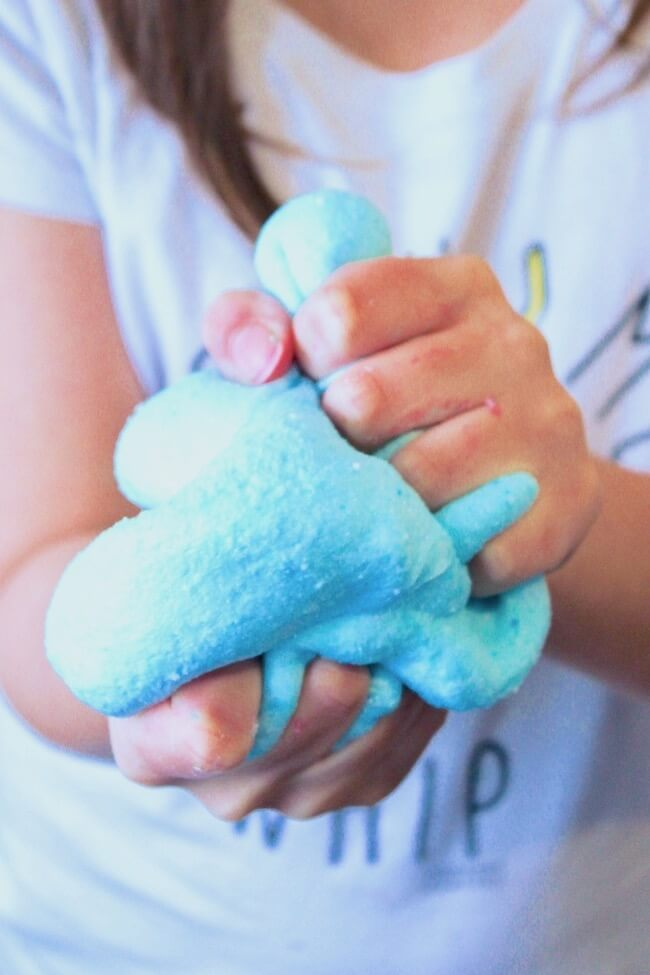 Squishing blue cotton candy cloud slime in hands