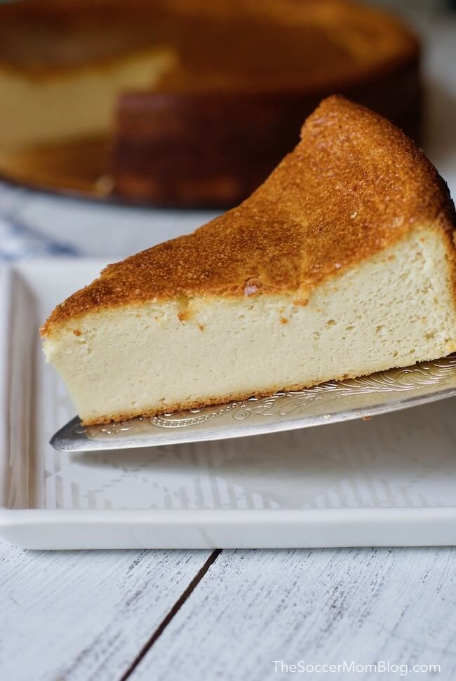 Placing cashew cheesecake on plate with a cake server
