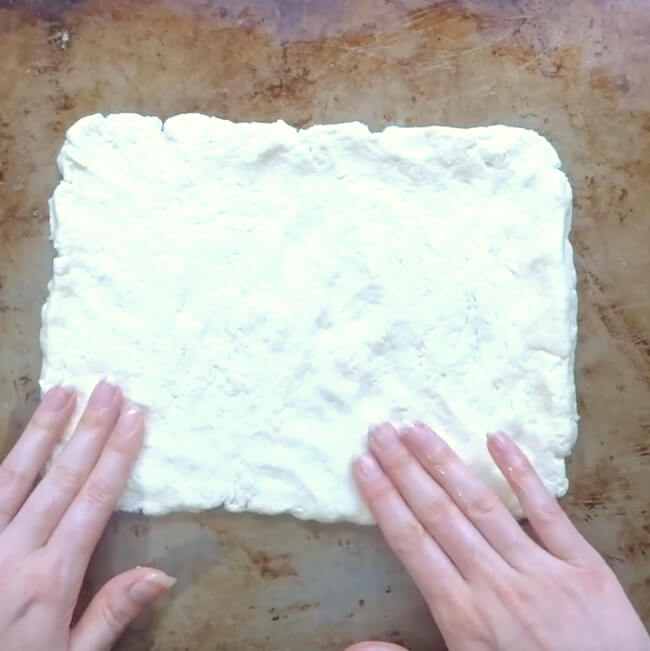 pressing gluten free pizza dough into a flag shape