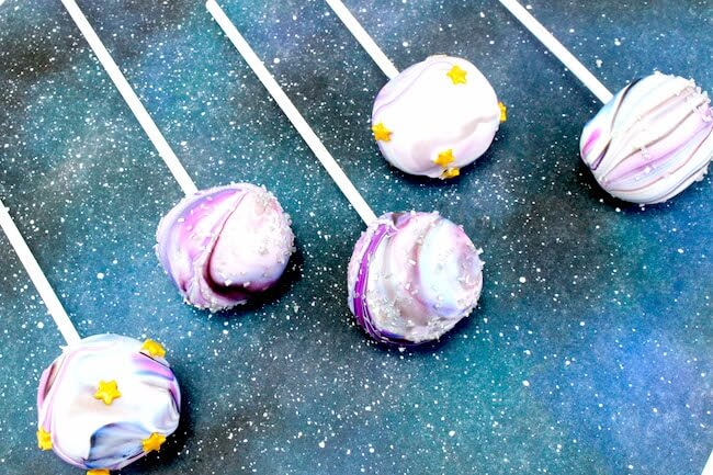 Space cake pops on blue galaxy background with stars