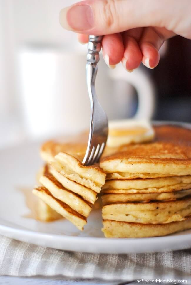 Cutting into a stack of fresh pancakes with coffee mug in background