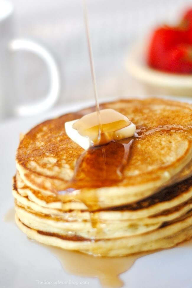 Pouring syrup over a stack of gluten free pancakes
