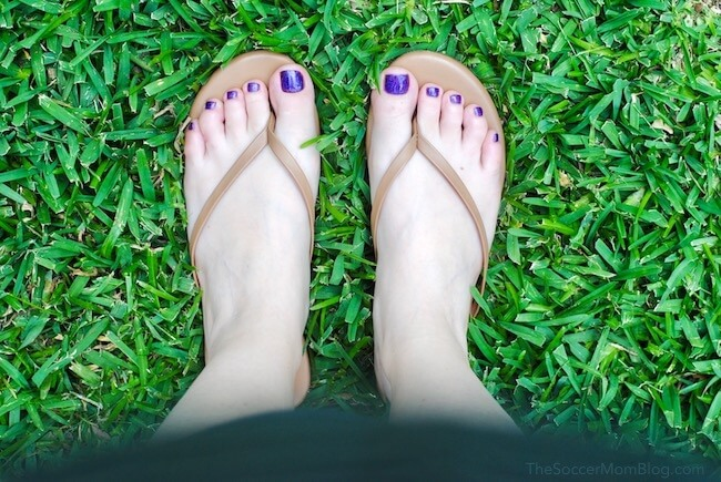 Freshly pedicured feet in sandals on green grass