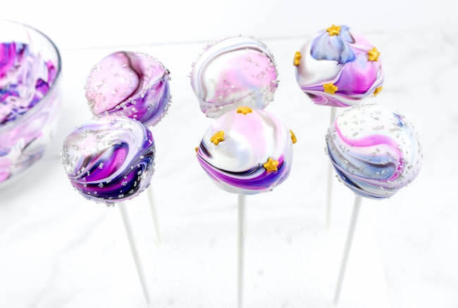Blue & purple galaxy cake pops on white background