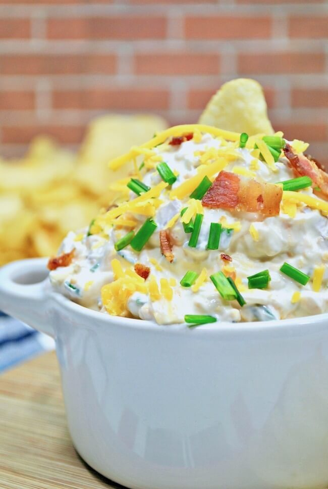 Close up of baked potato chip dip with bacon, cheese, and chives on top.