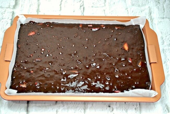 Brownie batter in baking pan with strawberries