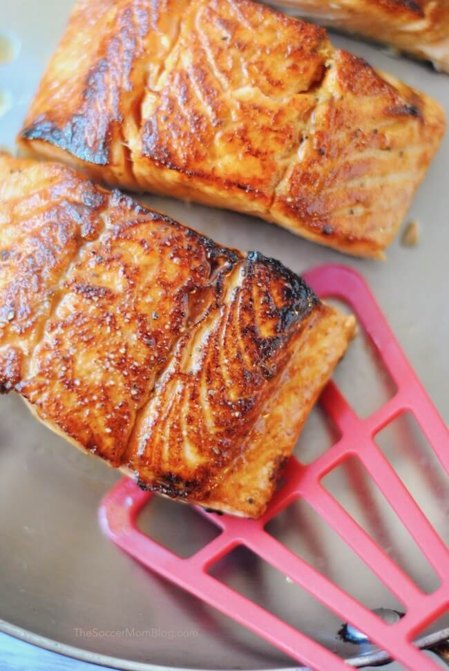 Flipping salmon filets in pan with fish spatula