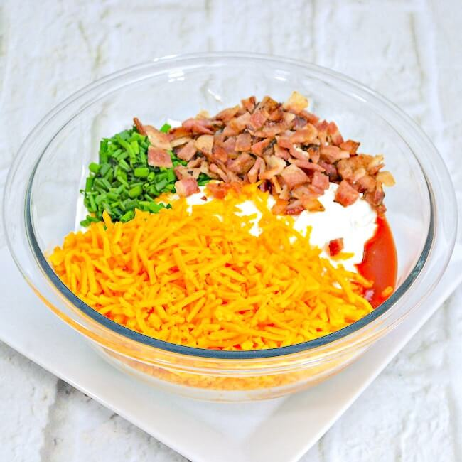 mixing bowl with loaded potato dip ingredients