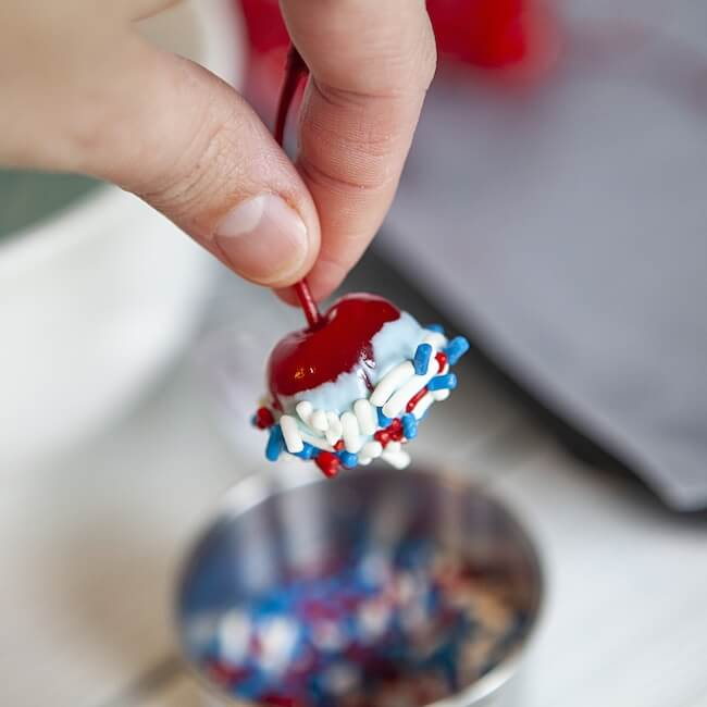 Dipping chocolate covered cherry in red white and blue sprinkles