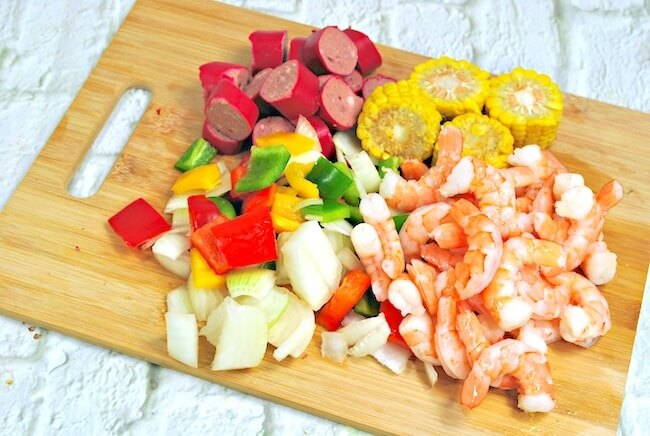 Chopped onions and peppers and shrimp on cutting board