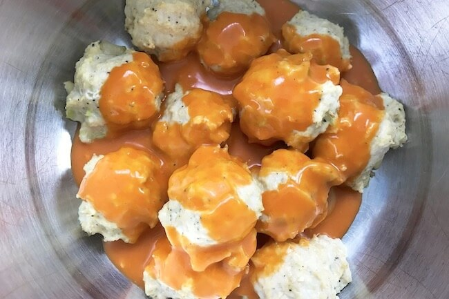 buffalo chicken meatballs coated in sauce in mixing bowl