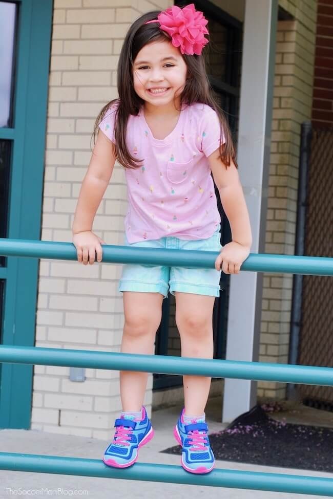 little girl climbing on fence at school