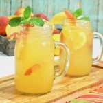 two mugs of peach lemonade on wooden cutting board