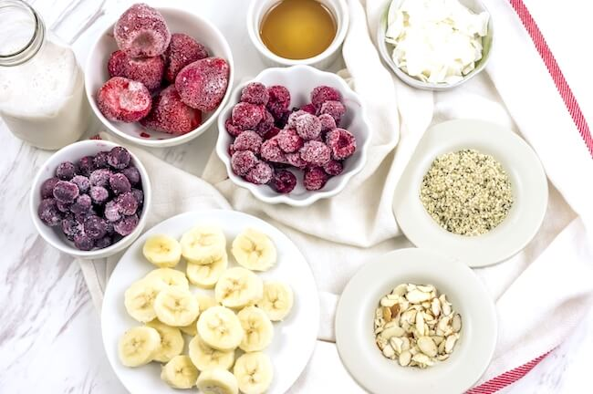 Berries, bananas, nuts, and seeds in bowls to make smoothies