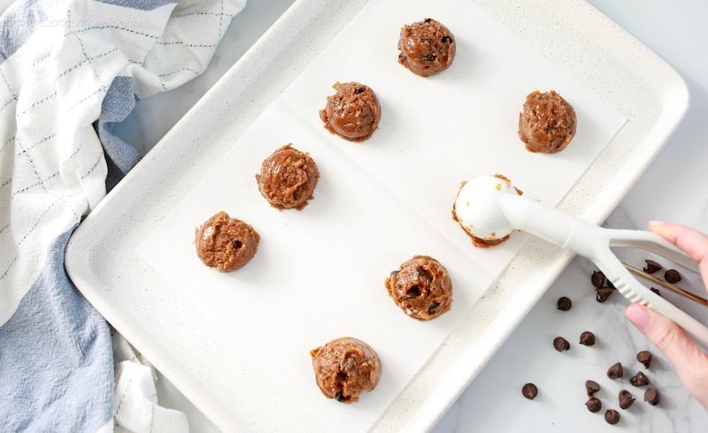 scooping chocolate chip cookies onto white baking sheet