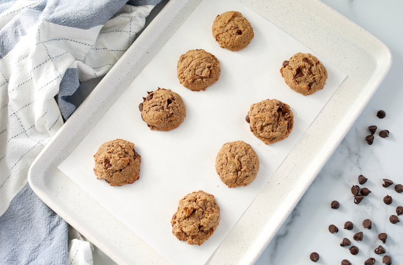 freshly baked chocolate chip cookies on white baking sheet