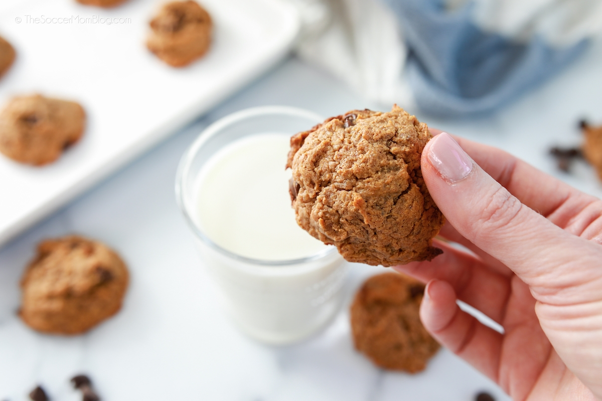 dipping chocolate chip cookie in glass of milk