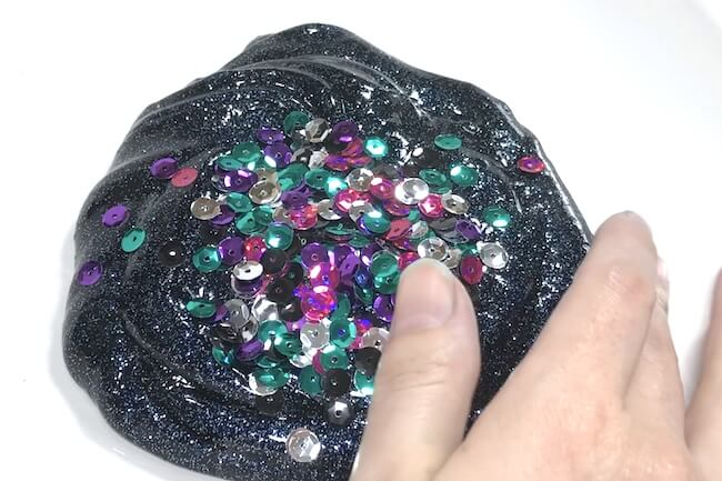 mixing sequins into galaxy slime