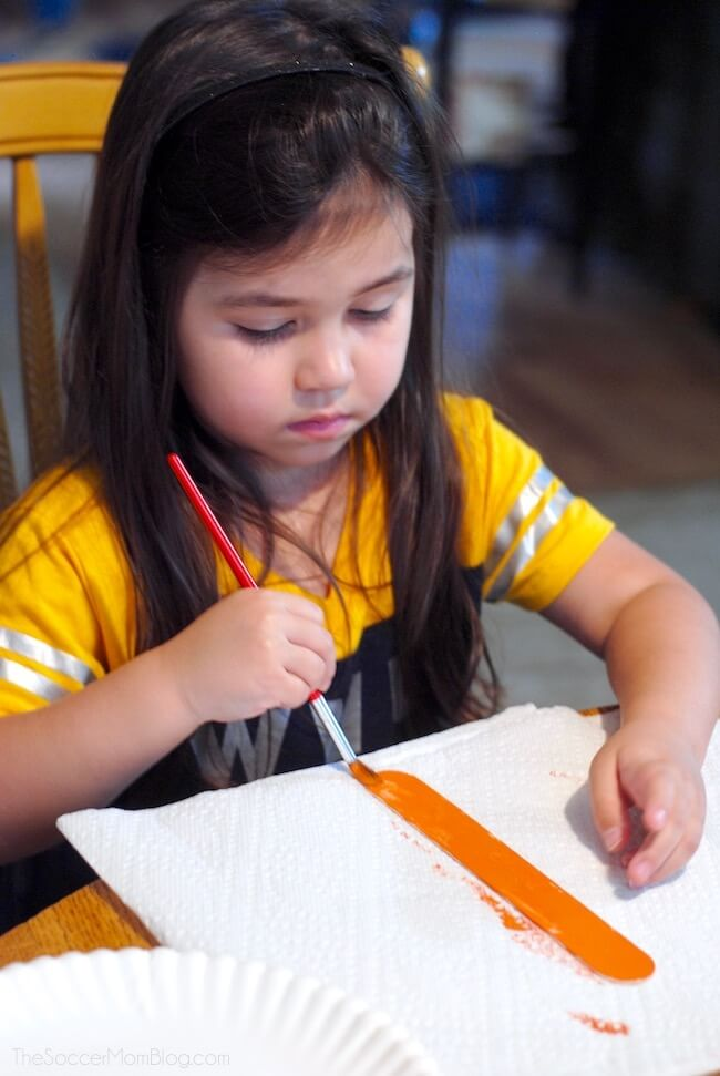 little girl painting a pumpkin made out of popsicle sticks
