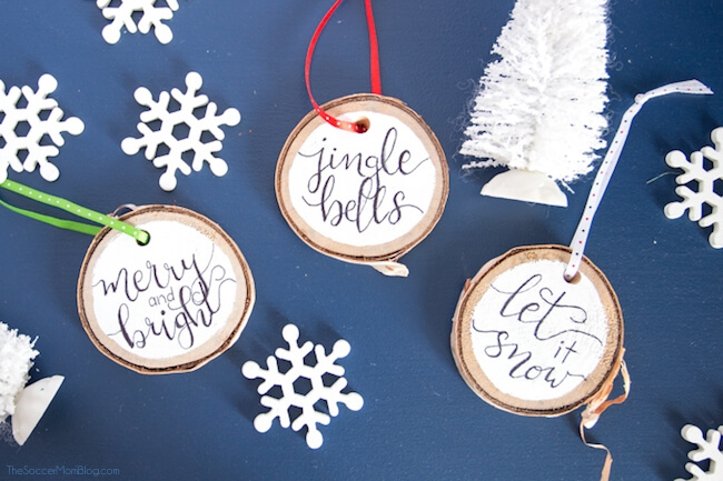 Click for easy VIDEO and photo step-by-step tutorial to make beautiful, rustic Hand Lettered Wood Slice Ornaments. Cute holiday craft for kids and adults!
