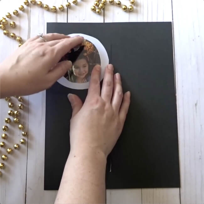 gluing child's photo on a New Year's eve craft