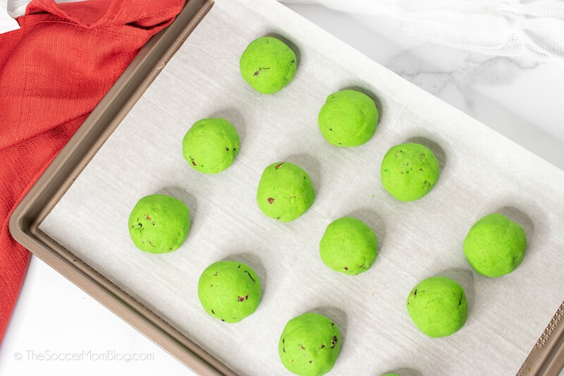 balls of green cookie dough on baking sheet