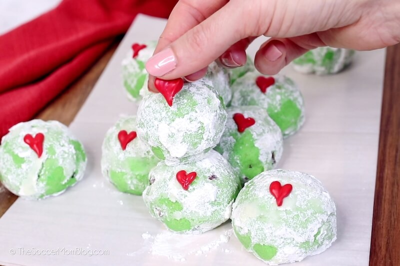 placing red heart decoration on Grinch snowball cookie