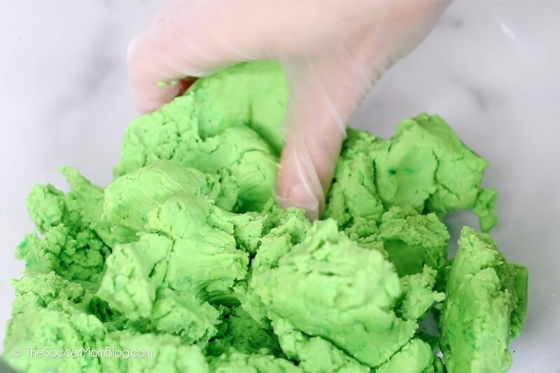 mixing green cookie dough by hand