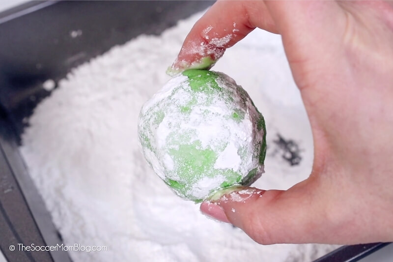 ball of green Christmas cookie dough coated in powdered sugar