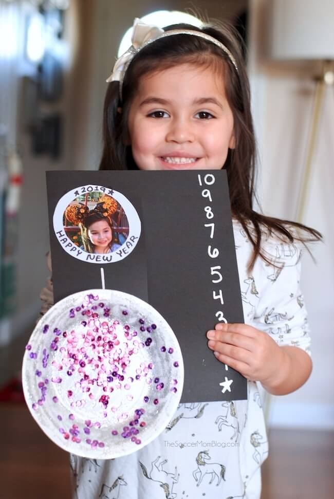 "Inside: Ring in the New Year with this adorable New Year's Eve Ball Drop Card! A commemorative countdown card that slides to reveal your child's photo. Kid-Made New Year's Eve Ball Drop Card Yesterday I was writing a check (fun, right?) and I paused while writing the date. Was it really 2018? It feels like just yesterday we were preparing for Y2K! But yes, here we are on the brink of 2019, with New Year's Eve barely over a week away! Our kids are still on the young side, so they don't stay up until midnight. However, we still want to include them in the festivities and find ways to make the night special. This New Year's Eve ball drop card is a fun and easy kid's craft for the occasion! They can make it to use for their own countdown, or as a keepsake to give to family. New Year's Countdown Card Supply List For your convenience in re-creating our New Year's Eve Ball Drop Photo Card, I've provided shop-able ad links to some of the products used; disclosure policy available here. Black card stock Small paper plate (6"") Silver glitter glue Sequins Metallic paint marker Child's photo Craft glue or glue gun Scissors How to Make a New Year's Eve Ball Drop Photo Card First, watch our quick video tutorial to see exactly how we made our easy New Year's Eve Ball Drop Card for kids. Then keep reading for full photo step-by-step instructions. Click video to play: [adthrive-in-post-video-player video-id=""jL2VKthz"" upload-date=""2018-12-23T01:59:36.000Z"" name=""NYE-card-Low"" description=""Ring in the New Year with this adorable New Year's Eve Ball Drop Card!""] The first thing we did was decorate our ball, so it would have plenty of time to dry. To decorate, we spread silver glitter glue to cover the entire surface of the paper plate. While the glue was still wet, we sprinkled sequins all over so that when the glue dried the sequins would stick to the plate. Feel free to customize your New Year's Eve ball with whatever sparkly supplies you have on hand - this is what we had at home and meant to be an idea starter. You could also use metallic silver paint, paint markers, loose glitter, plastic jewels, aluminum foil, etc. While your glitter ball dries, you can work on the rest of the New Year's card. Cut a slit in the middle of your black card stock, vertically, leaving about one inch uncut at the top and bottom. Use a metallic paint marker to write a countdown on the right side of your paper, from 10 to 1. On the top left corner of your card, glue your child's photo. You may need to trim the photo so that none of it is showing when the glitter ball is on top of it. When your glitter ball is dry, glue one end a jumbo craft stick to the back of the paper plate. Slide the craft stick through the slit in your black card stock, so that the glitter ball is on top of the left side of the card stock, and that the rest of the craft stick is behind the card on the right side. Now you can slide the New Year's Eve ball up and down your card, using the craft stick. Have fun and customize your card with New Year's messages and any special decorations you like! More New Year's Eve Fun for Kids Be sure to check out our list of more than 25 of our favorite easy New Year's Eve activities for kids too:"